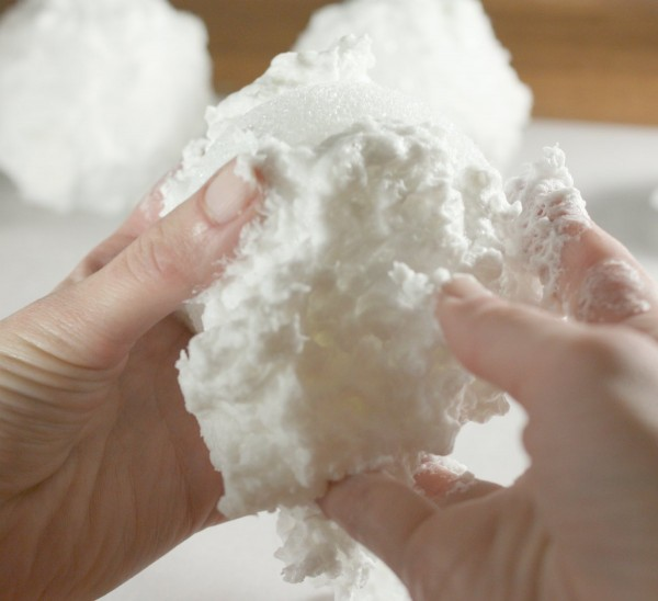 Mooshing faux snow on the styrofoam balls