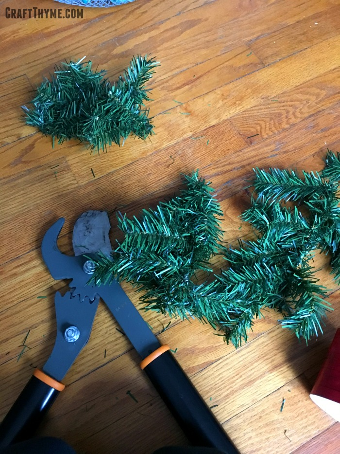 Cutting garland to thicken a sparse Christmas Tree.